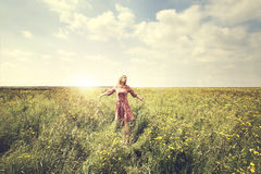 Dreamy woman walking in nature illuminated by the sun Royalty Free Stock Image