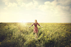 Dreamy woman walking in nature towards the sun. In a surreal place Stock Photography