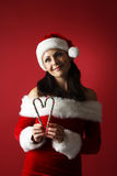 Dreamy woman wearing santa claus clothes holding candy cane shape heart on red background Stock Image