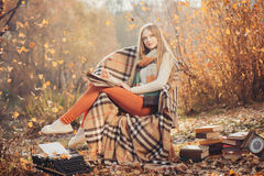 Dreamy woman writing in the autumn park Stock Photos