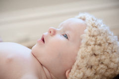 Dreamy Wonder. Baby laying on their back looking upward wearing a knit hat with a look of surprise or wonder on their face Royalty Free Stock Photo