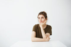 Dreamy young beautiful girl student sitting at table dreaming thinking over white background. stock photo