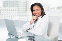 Dreamy young dark haired businesswoman using a laptop Royalty Free Stock Images
