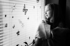 Dreamy Young girl. Little girl sitting at the window and looking through it with a smile on her face stock image