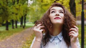 Dreamy young redhead woman in a park. HD stock footage