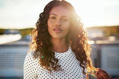 Dreamy young woman backlit by the rising sun. Standing on an urban rooftop playing with her gorgeous long curly hair as she stares at the camera Royalty Free Stock Images