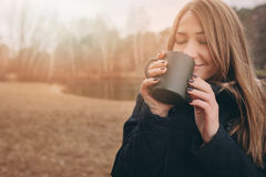 Dreamy young woman drinking hot tea outdoor on the walk, enjoying traveling in autumn Royalty Free Stock Image