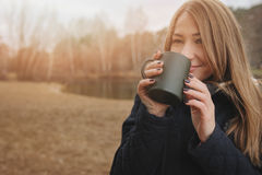 Dreamy young woman drinking hot tea outdoor on the walk, enjoying traveling in autumn Stock Image