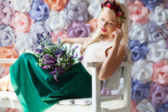 Dreamy young woman in flower diadem sitting on the white bench w Royalty Free Stock Photo