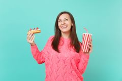 Dreamy young woman in knitted pink sweater looking up hold in hands eclair cake, plastic cup of cola or soda isolated on. Dreamy young woman in knitted pink stock photo