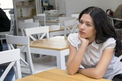 Dreamy young woman posing inside. Portrait of pensive brunette model sitting in cafe with nice interior and looking away. Brooding girl waiting for order. Copy royalty free stock photo