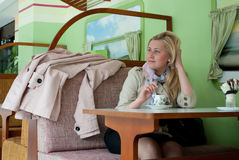 Dreamy young woman sitting in a cafe with a cup of coffee. Young beautiful blond woman sitting in cafe drinking coffee Stock Images