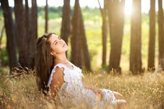 Dreamy young woman sitting in field with sunlight in background. Portrait of a dreamy young woman sitting in field with sunlight in background royalty free stock photo