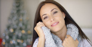 Dreamy young woman snuggling into her scarf Stock Images