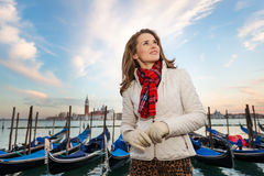 Dreamy young woman traveler standing on embankment in Venice Stock Image