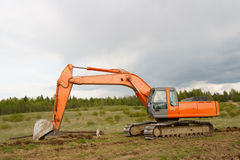 Dredge. The orange dredge against green forest Royalty Free Stock Images