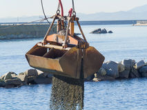 Dredge Clamshell Bucket unloading gravel in the water of a port Stock Images