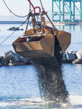 Dredge Clamshell Bucket unloading gravel in the water of a port Stock Photography