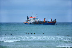 Dredge in seawater. Big dredge in seawater and surfers Royalty Free Stock Photo