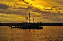Dredge working in a marina, with yellow sunset. royalty free stock photos