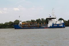 Dredger for absorption of trailer bunker during work on land rec. Lamation for new ports. Suction dredge. Dredging in fairway of Dinai River. Cutter suction royalty free stock photography