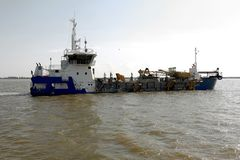 Dredger for absorption of trailer bunker during work on land rec. Lamation for new ports. Suction dredge. Dredging in fairway of Dinai River. Cutter suction stock image