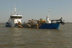 Dredger for absorption of trailer bunker during work on land rec. Lamation for new ports. Suction dredge. Dredging in fairway of Dinai River. Cutter suction royalty free stock images