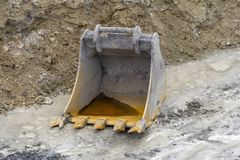 Dredger bucket. Old dredger bucket on loamy ground Stock Images