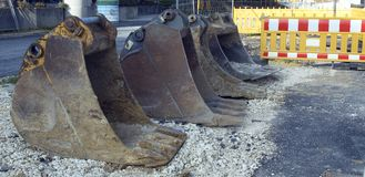 Excavator shovels. Dredger buckets lying in a row at construction site Stock Photos