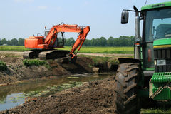 Dredger digging ditch. Dig ditches and maintain them for a good removal of overflowing water Royalty Free Stock Image