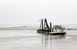 Dredger in Dollard near Nieuw Statenzijl, Netherlands. The Dollard area, which borders the Eems estuary, came into existence between 1280 and 1550 approximately Stock Photos