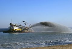 Dredger pumps sand onto beach Stock Images