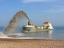 Dredger replenishing beach at  Eastbourne,  England, Uk. Shingle being deposited after Winter storms Royalty Free Stock Photography