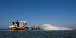 Dredger at sea. A trailing suction hopper dredger Rain bowing royalty free stock photo