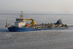 Dredger ship in icy harbor. A dredger ship passes through a ice-filled harbor Stock Photos