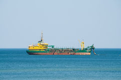 Dredger ship working at sea Royalty Free Stock Image