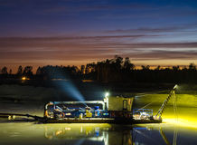 Dredger working durimg sunset. Royalty Free Stock Photography