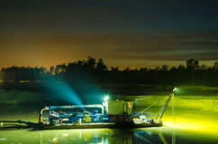 Dredger working durimg sunset. Stock Images