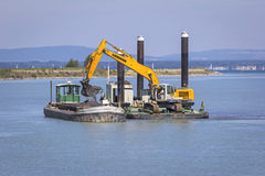 Dredger is working, near Bregenz, Austria. A Dredger is working to clear the River Rhine at the beginning of the Lake Constance (Bodensee) near Bregenz in Royalty Free Stock Photography