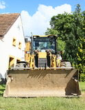 Dredger. Yellow dredger standing on grass in front of white village family house and green tree Stock Photography