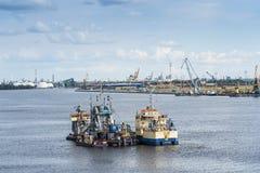 Dredgeren och hopperen rusar in farleden Riga Arkivfoto