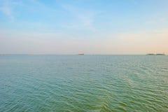 Dredgers som muddrar för sand i en sjö på solnedgången Arkivbild