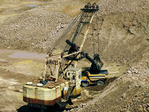 Dredges and dump truck. Belaz in career on extraction of minerals royalty free stock image