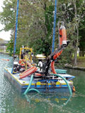 Dredging Equipment in River Canal. Water restoration dredging project is removing invasive algae from canals in Crystal River, Florida, habitat for the Stock Photos