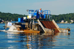 Dredging the Lake. A worker performs environmental work on a lake in New Jersey Royalty Free Stock Images