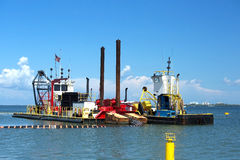 Dredging and multi purpose boat work together on the Gulf of Mexico. Dredging vessel and a multipurpose work boat work side by side as they excavate sand at Fort Stock Photography