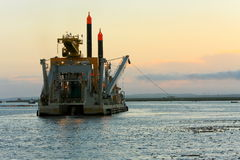Dredging vessel operating at sunset. royalty free stock photography