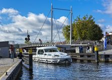 A motor yacht passes the rotary bridge in the city of malchow in brandenburg stock image