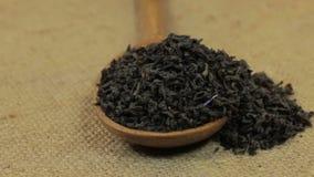 Drehen eines Löffels, laufend mit dem schwarzen Tee des Blattes über und liegen auf Leinwand stock video