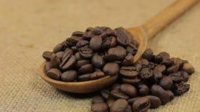 Drehen eines Löffels, laufend mit den Kaffeebohnen über und liegen auf Leinwand stock footage